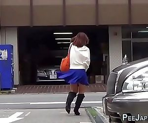 Asian whore pees behind car..